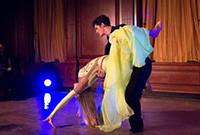 A ballroom dancing duo, with a male holding a reclining woman.