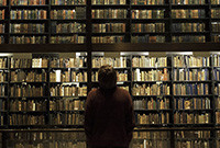 A silhouetted figure in front of bookstacks at Yale's Beinecke Library.