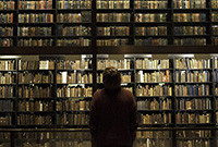 A man looking at stacks of books at Beinecke Library.