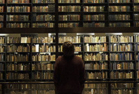 A woman seen from the rear standing, looking at the book stacks in the Beinecke Rare Book and Manuscript Library.
