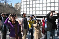 A group of people with binoculars studying birds.