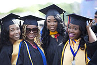 A photo of four black female students in college graduation attire.