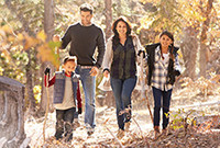 Parents with their son and daugther walking through the woods.