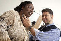 A white male doctor examing a black woman patient.