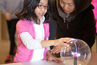 A girl and her mother inspecting a science experiment involving a glass globe containing an electrical charge.
