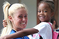 A white teenage girl holding a young black girl.