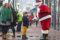 Santa shaking hands with a little boy on the street.