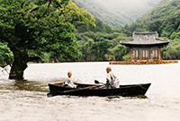 A boat carrying a Buddhist monk and a young boy, with a small temple in the background.