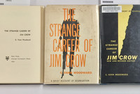 """Different editions of C. Vann Woodward's book """"The Strange Career of Jim Crow"""" on display."""