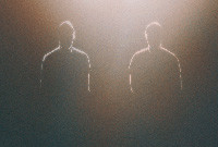 The silhouettes of two young males in a darkened room.