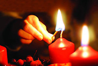 An image of a person's hand lighting a red candle.