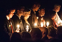 Singers in an ensemble holding candles in a darkened environment.