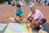 A middle-aged man and a young woman stooping next to chalk artwork on a sidewalk.
