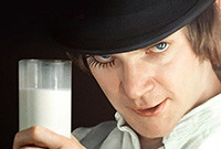 """A scene from """"A Clockwork Orange,"""" depicting a young male holding up a glass of milk."""