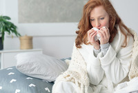 A woman with a cold, who looks very unhappy.