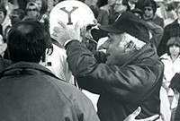 Carmen Cozza, Yale's longtime head football coach, holdng the head of a football player.