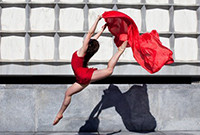 A student dancer in mid-air holding a section of red fabric.