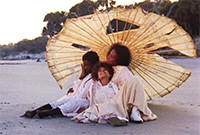Three young women sitting on a beach beneath a large white umbrella.