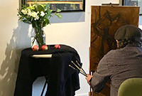 A photo of an artist painting a vase of flowers.