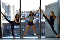 Three female dancers with their limbs outstretched in front of a large window overlooking a city.