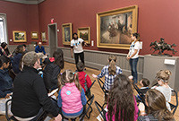 Children listening to an adult delivering a lecture at an art gallery.