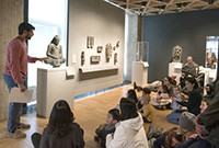 A tour guide explaing artworks to a group of children at an art gallery.
