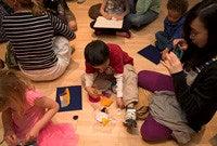 Children sitting on the flooor of an art gallery making artworks.