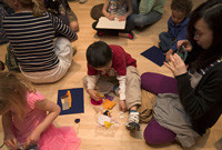 Children sitting on the flooor of an art gallery making artworks.