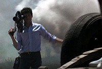 """A still from the film """"Medium Cool"""" showing a camerman filming an overturned vehicle"""