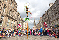 A woman on tightrope in a city street, juggling hoops with her arms and her right leg.