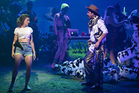 "A scene from a play, ""Girls,"" depicting a young owman in blue shorts and a man in a cowboy outfit."