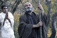 """A scene from the film """"Katho Upanishad,"""" depicting a young man praying and an older man looking skyward."""