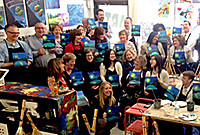 A gathering of Yale employees with canvases they painted.