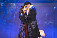 A male and female opera singer embracing on stage.