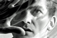 "A still from the film ""Orpheus,"" showing a man holding up his right hand in front of his face."