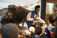 A young black woman holding an animal skull in front of a group of children at the Peabody Museum of Natural History.