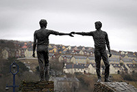 A sculpture of two men reaching out to shake hands.