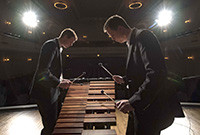Two male percussion players at an instrument.