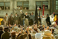 "A still from the film ""Peterloo,"" depicting a man giving a speech outdoors to a group of people."