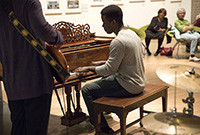 A young black male playing a piano.
