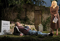 "A scene from the play ""The Plot,"" showing a man laying down on his burial plot looking up at a blonde woman."