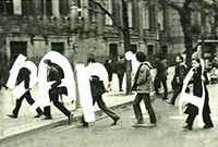 Five people walking across a street carrying large letters over white letters over their bodies.