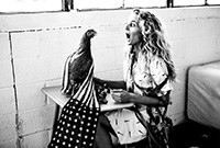 The artist Kathryn Hamilton sitting at a table on which a chicken is draped by the American flag.