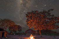 A man sitting at an open fire in a village under a starry sky in Africa.