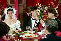 "A photo of a scence from the film ""The Wedding Banquet,"" depicting the wedding party at a table."