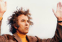 "A still from the film ""The Wicker Man,"" showing Christopher Lee holding up his arms."