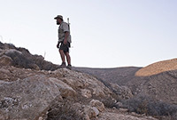 Still from the documentary 'Wild West Hebron,' showing a man with a rifle strung on his shoulder, standing on a ridge.