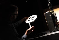 Person in a projection booth examining a strip of film.