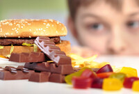 Young boy looking at junk food and candy