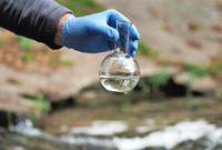 A hand in a latex glove holding a beaker full of water, with an outdoor stream in the background.